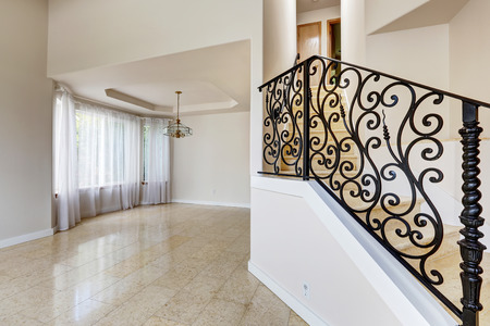 iron curtain: Emtpy house interior with shiny tile floor and brith white walls. Marble staircase with black wrought iron railing Stock Photo