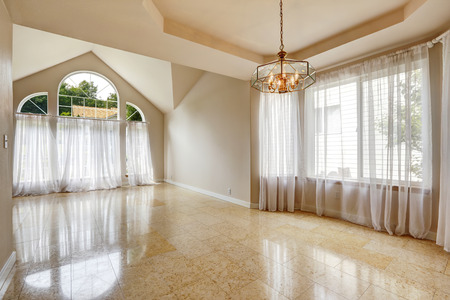 vaulted ceiling: Emtpy house interior with shiny marble  tile floor. Hight vaulted ceiling with large windows and transparent white curtains Stock Photo