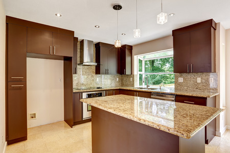 Modern kitchen room with matte brown cabinets, shiny granite tops, steel stove with hood, granite back splash trim and marble tile floor photo