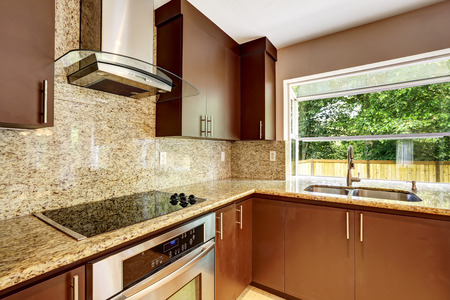 Modern kitchen room with matte brown cabinets, shiny granite tops, steel stove with hood and granite back splash photo