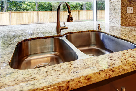sink: Kitchen cabinet with double steel sink and granite counter top. Close up view