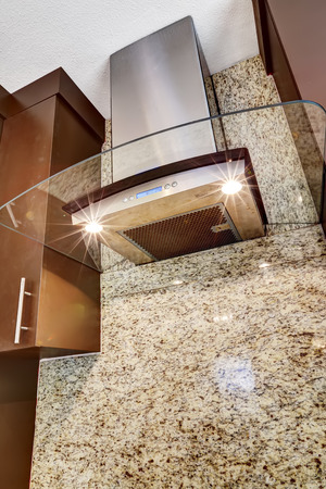 back kitchen: Modern kitchen appliance. Steel hood with glass element and lights on blend perfectly with granite back splash trim