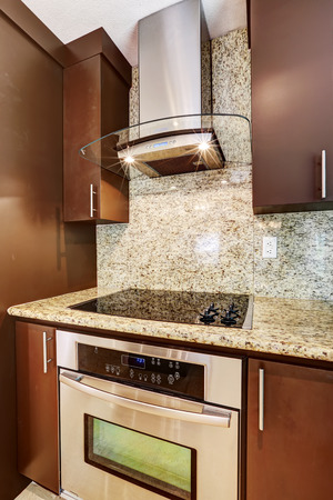 back kitchen: Modern kitchen appliance. Steel hood with glass element and lights on blend perfectly with steel stove with flat black shiny surface