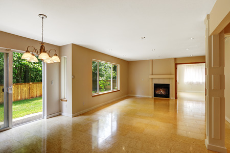 shiny floor: Empty living room with shiny marble tile floor and fireplace. Room has exit to backyard area
