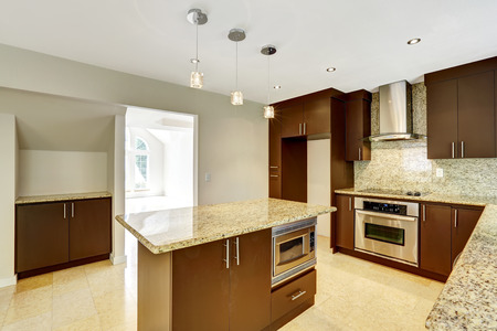 Modern kitchen room with matte brown cabinets, shiny granite tops, steel stove with hood and granite back splash Stock Photo