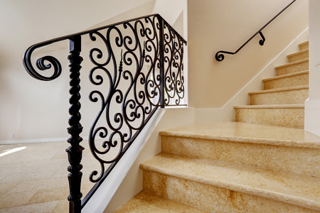 staircase: Emtpy house interior with shiny tile floor. Marble staircase with black wrought iron railing