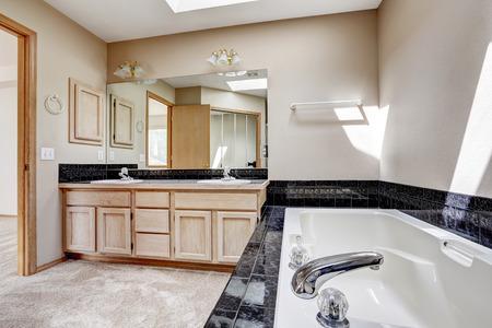 white trim: Bright bathroom interior with carpet floor, white bath tub with black granite tile trim. Vanity cabinet with granite top and large mirror Stock Photo