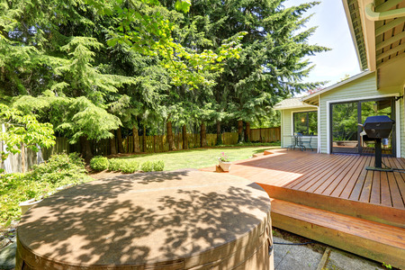 Wooden walkout patio with barbecue and jacuzzi photo