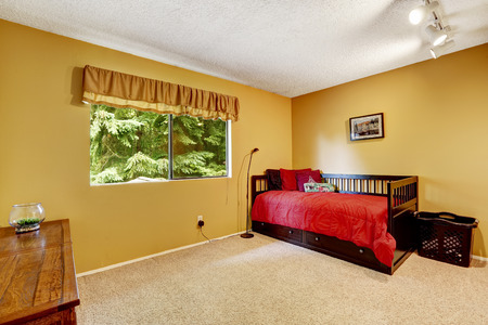 Single wooden bed with drawers and bright red bedding. Bedroom in light yellow tones