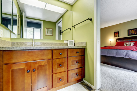 master bath: Light green tone bathroom in master bedroom. New wooden cabinet with drawers and granite top