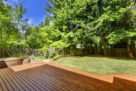 Wooden walkout patio and fenced backyard photo