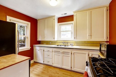 cabinets: White kitchen cabinets with bright red wall in old house