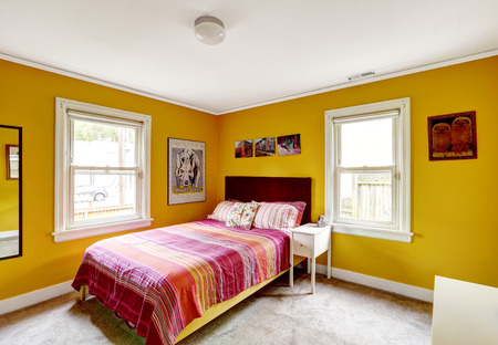 idea comfortable: Bedroom in bright yellow color with single bed. Red stripped bedding Stock Photo
