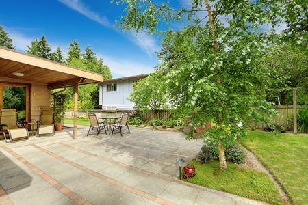 Achtertuin met uitloop patio. Berk boom groeit op de achtertuin gebied