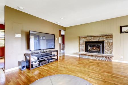Living room with stone trim fireplace and tv. Hardwood floor and beige walls 版權商用圖片