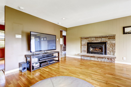 Living room with stone trim fireplace and tv. Hardwood floor and beige walls Stockfoto