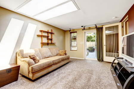 skylights: Living room with skylight and exit to backyard, Comfortable beige sofa