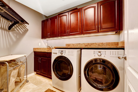 dryer  estate: Modern laundry room interior with whtie appliances and bright wooden cabinets with granite tops Stock Photo