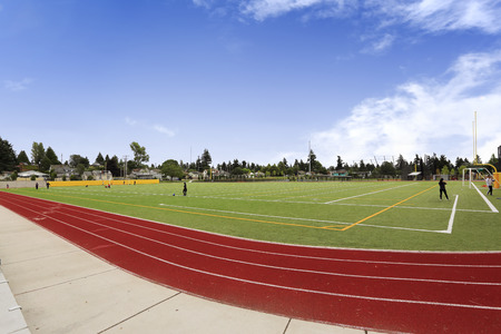 Large football field and bright red running rack. School sport yard