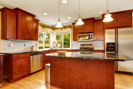 Bright kitchen room with windows. Room has large steel refrigerator and kitchen island