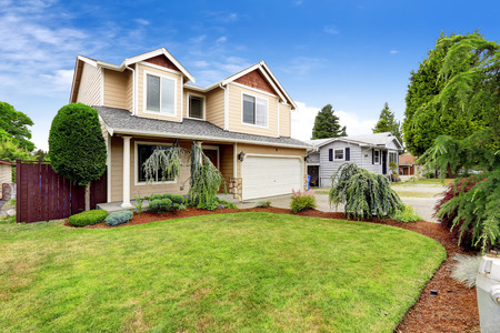 House exterior with beautiful curb appeal. Green lawn with brown sawdust and decorative trees