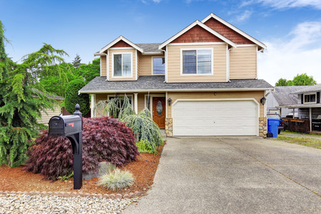 House exterior with beautiful curb appeal. Garage with stone trim and driveway Stock Photo