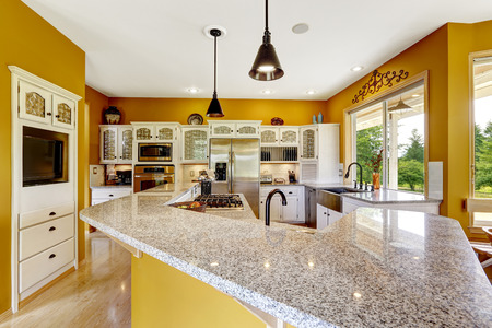 kitchen island: Farm house interior. Luxury kitchen room in bright yellow color with big island and granite top.