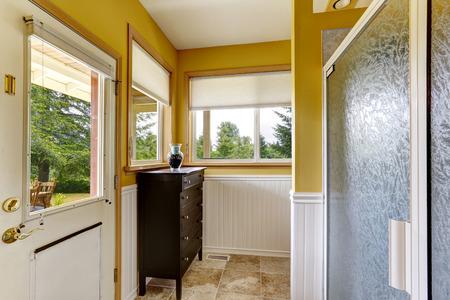 white trim: Farm house interior. Bright yellow wall with white trim. Bathroom has exit to backyard Stock Photo