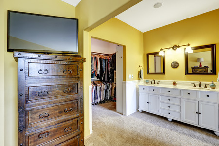 walk in closet: Bright yellow room with white vanity cabinet, wooden dresser with tv and walk-in closet