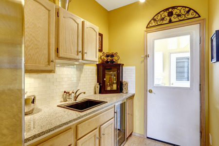 kitchen cabinets: Bright yellow small kitchen area with wooden cabinets and granite top Stock Photo