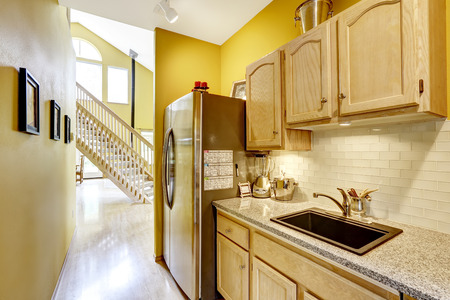 granite kitchen: Bright yellow small kitchen area with wooden cabinets and granite top. View of wooden staircase. Farm house interior