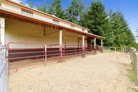 Horse barn with outside stables separated with red railings