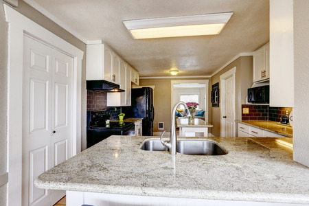 brich: Kitchen cabinet with granite top and steel sink in kitchen room with brich tile back splash trim