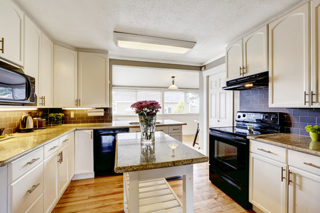 kitchen cabinets: White kitchen cabinets with black appliances. Kitchen island with granite top decorated with flowers