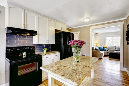 black appliances: White kitchen cabinets with black appliances. Kitchen island with granite top decorated with flowers