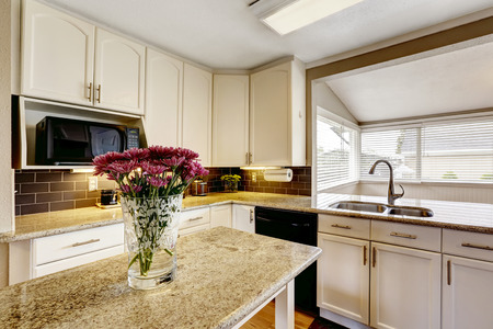 kitchen island: White kitchen cabinets with black appliances. Kitchen island with granite top decorated with flowers