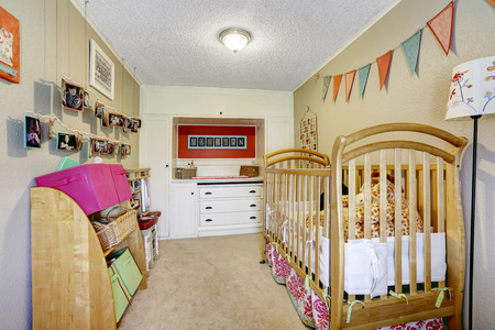 kids bedroom: Small baby room interior with wooden crib and  built-in storage combination with drawers