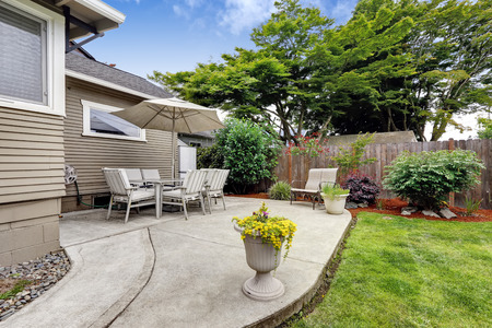 Backyard patio area with table set and umbrella. Patio with concrete floor and flower pots Banque d'images