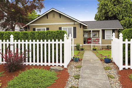 American house exterior with curb appeal. White wooden fence with concrete walkway