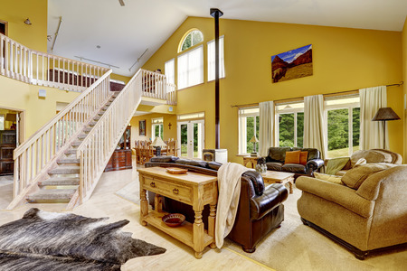 Beautiful luxury house with high vaulted ceiling and loft with wooden staircase. Spacious family room with leather couches and antique stove photo