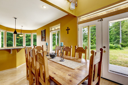 dining table and chairs: Beautiful dining table with chairs in farm house. Bright yellow dining area with exit to backyard