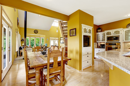 Beautiful farm house interior in bright yellow color. Wooden dining table set in kitchen with white cabinets and granite tops