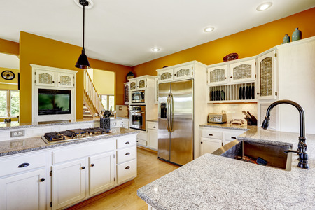 Farm house interior. Luxury kitchen room in bright yellow color with white cabinets, steel appliances and granite