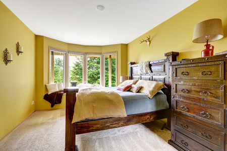 Farm house interior. Luxury bedroom interior. Beautiful wooden high bed with large dresser photo