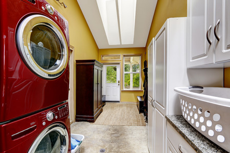 laundry room: Bright yellow hallway with laundry area, wardrobe and exit to backayrd Stock Photo