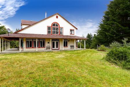 american house: American farm house exterior with wraparound deck Stock Photo