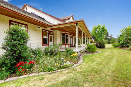 front porch: Farm house exterior with front yard landscape . Entrance porch with columns Stock Photo