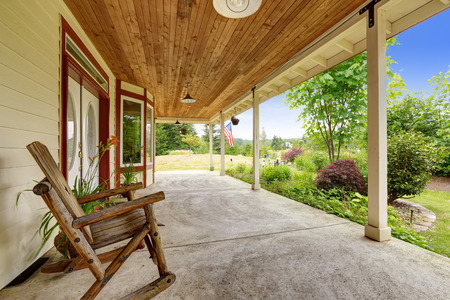 Farm house exterior with front yard landscape . Spacious entrance porch with rocking chair