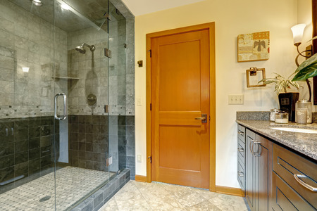 shower: Modern bathroom interior with glass door shower and tile wall trim. Bathroom with bright orange door