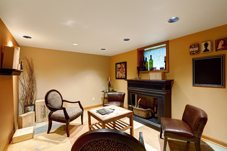basement: Cozy sitting area in basement room with decorative fireplace, chairs and small wooden table Stock Photo